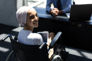 Portrait of happy disabled young mixed-race female executive holding digital tablet in modern office. she is smiling at camera